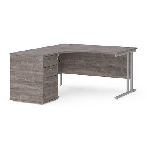 Maestro 25 left hand ergonomic desk 1400mm with silver cantilever frame and desk high pedestal - grey oak